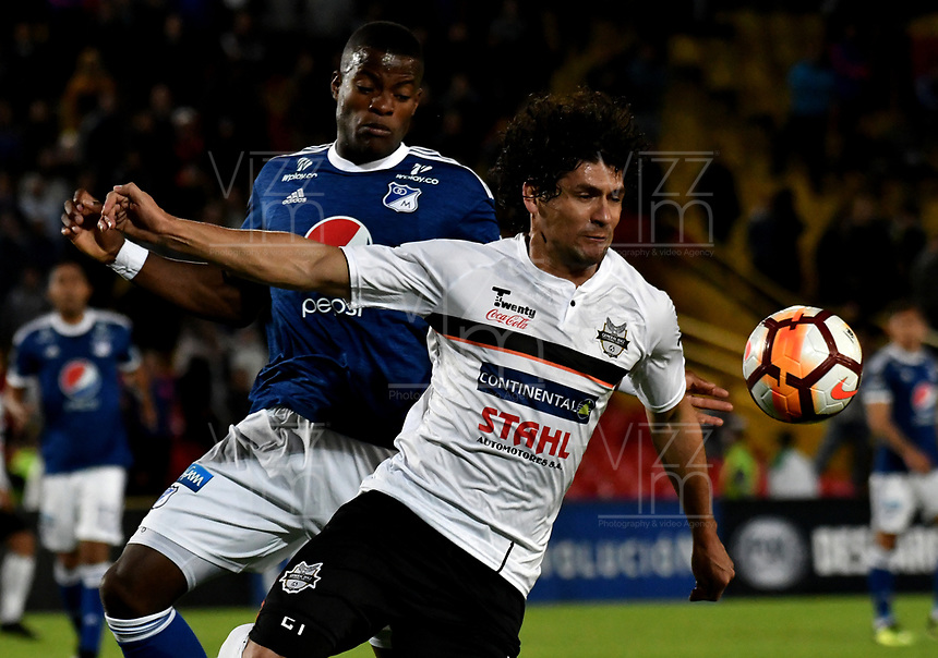 BOGOTÁ - COLOMBIA, 15-08-2018: Andrés Román (Izq.) jugador de Millonarios (COL), disputa el balón con Blás Cáceres (Der.) jugador de General Díaz (PAR), durante partido de vuelta entre Millonarios (COL) y General Díaz (PAR), de la segunda fase por la Copa Conmebol Sudamericana 2018, en el estadio Nemesio Camacho El Campin, de la ciudad de Bogotá. / Andres Roman (L) player of Millonarios (COL), fights for the ball with Blas Caceres (R) player of General Diaz (PAR), during a match of the second leg between Millonarios (COL) and General Diaz (PAR), of the second phase for the Conmebol Sudamericana Cup 2018 in the Nemesio Camacho El Campin stadium in Bogota city. VizzorImage / Luis Ramirez / Staff.
