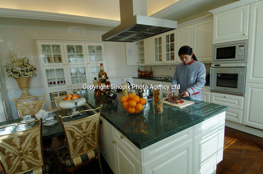 A maid prepares food in the main kitchen of the Palais de Fortune luxury development in Beijing, China. The development consists of 172 luxury mansions selling for over 2 million pounds each. The development is a heaven for China's super-rich terrified of kidnap and murder. The mansions are packed together and will form a dense community of millionaires..04 Feb 2006