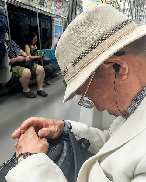 A senior Japanese man sleeping on a train. Like many Tokyoites, he has an instinct that wakes him exactly the moment a train arrives to his station.
