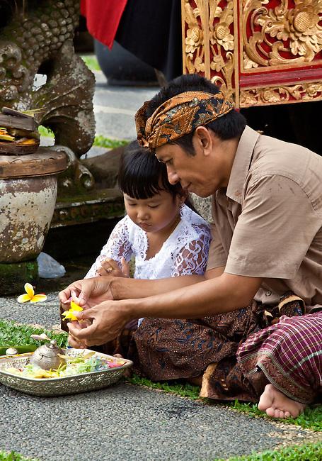 Father and daughter make puja at PURA TAMAN SARASWATI during the GALUNGAN FESTIVAL - UBUD, BALI, INDONESIA