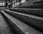 A young woman walking up steps in an urban environment