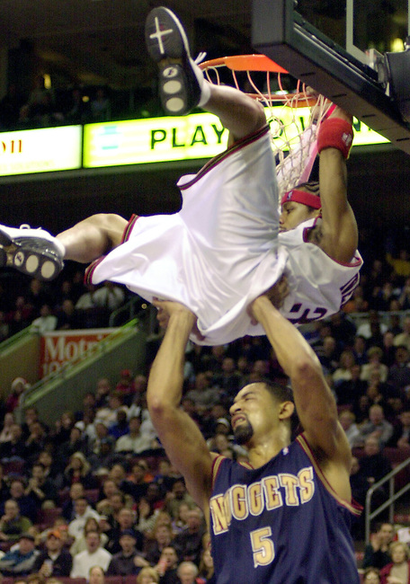 Philadelphia 76ers guard Alan Iverson (3) is fouled under the basket by Denver Nuggets forward Juwan Howard (5) in the second quarter of play Dec. 16, 2002 in Philadelphia. (AP Photo/Brad C Bower)