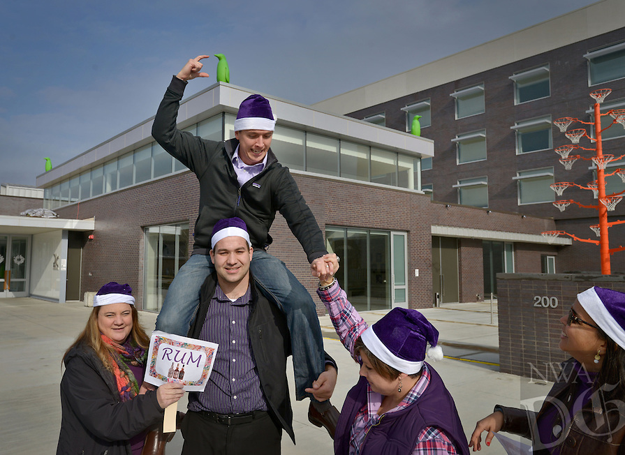 STAFF PHOTO BEN GOFF  @NWABenGoff -- 12/11/14 Valerie Thomas, from left, Nolan Pedduto and Jennifer Allison give Matt Schilb a boost while setting up a forced perspective photo of Schilb appearing to grab one of the penguin statues on the roof of 21c Museum Hotel with their team 'The Purple Pa rum pa pum pums,' while competing with other teams of employees from Nielsen in a photo scavenger hunt team building exercise in downtown Bentonville on Thursday Dec. 11, 2014.