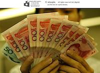 A shop keeper shows RMB, Shenzhen, China..