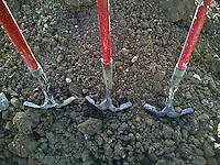 Three red-handled shovels at gravesite at cemetery. From Palm Pre camera.