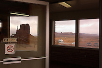 One of the easily-recognizable mitten buttes reflects in a glass door at the visitor center at the Monument Valley Navajo Tribal Park in southern Utah, Friday, March 10, 2006. The stunning vistas in the park, stars in many John Ford westerns, are an often-forgotten destination for American travelers. (Kevin Moloney for the New York Times)