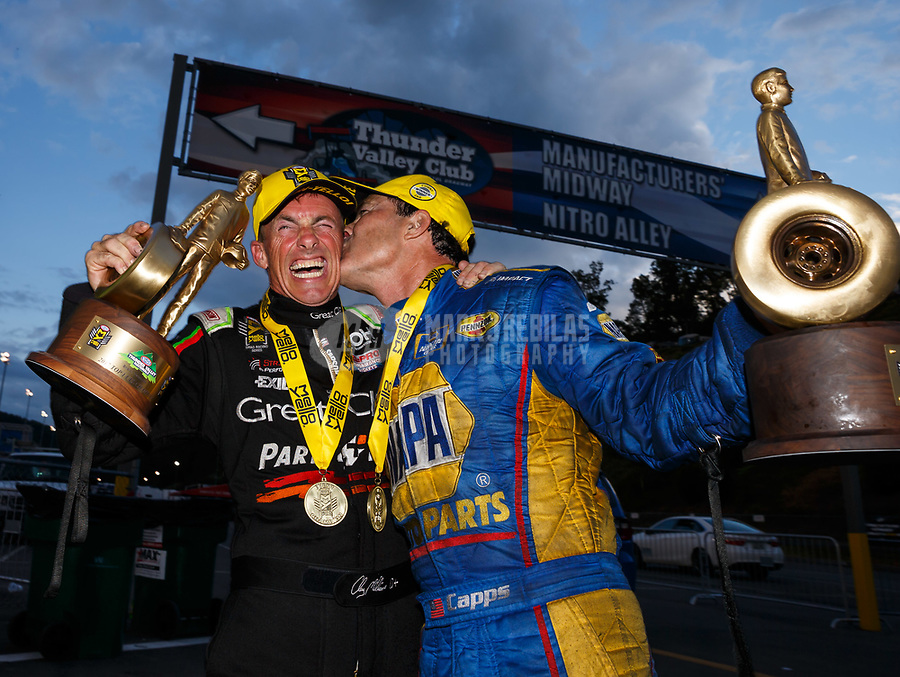 Jun 18, 2017; Bristol, TN, USA; NHRA funny car driver Ron Capps (right) kisses top fuel driver Clay Millican as they celebrate after winning the Thunder Valley Nationals at Bristol Dragway. Mandatory Credit: Mark J. Rebilas-USA TODAY Sports