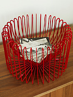 A retro red plastic covered wire bowl stands on a wooden sideboard, inside are black and white postcards.