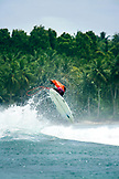 INDONESIA, Mentawai Islands, Kandui Surf Resort, surfer getting air off of a wave with palm trees in background