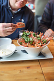 CANADA, Vancouver, British Columbia, a man eats fried shrimp heads at a local bistro, Edible Canada, located on Granville Island