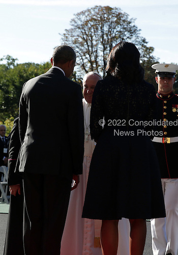 U.S. President Barack Obama and first Lady Michelle Obama welcome Pope Francis in an arrival ceremony at the White House on September 23, 2015 in Washington, DC. The Pope begins his first trip to the United States at the White House followed by a visit to St. Matthew's Cathedral, and will then hold a Mass on the grounds of the Basilica of the National Shrine of the Immaculate Conception.  <br /> Credit: Alex Wong / Pool via CNP
