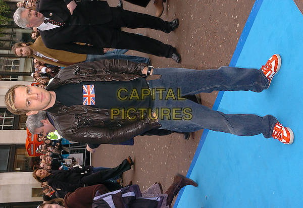 EWAN McGREGOR.Valiant Premiere, Odeon West End, Leicester Square.March 20th, 2005.full length black leather jacket hands in pockets union jack flag red orange and white shoes.www.capitalpictures.com.sales@capitalpictures.com.©Capital Pictures