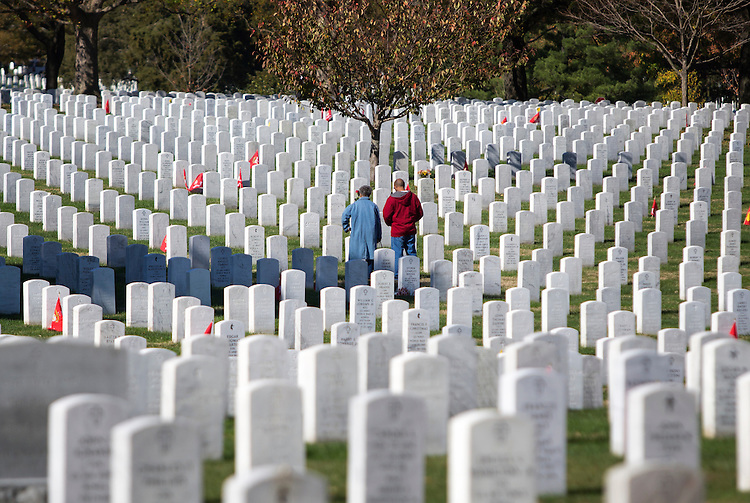 UNITED STATES - NOVEMBER 11 - A man and woman stand alone at a grave during Veterans Day at Arlington National Cemetery, in Arlington, Va., Wednesday, November 11, 2015. (Photo By Al Drago/CQ Roll Call)