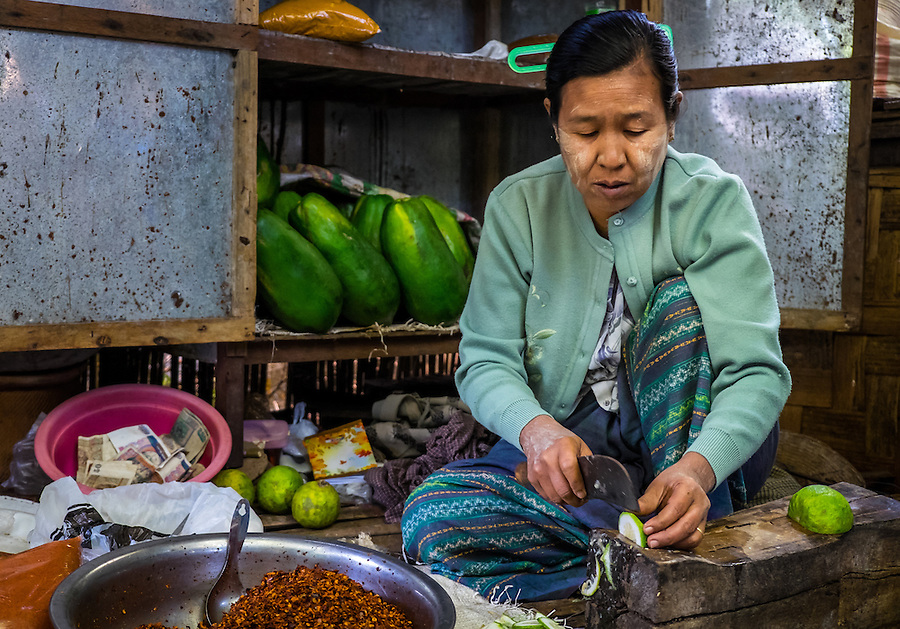 BAGAN, MYANMAR - CIRCA DECEMBER 2013: Woman cutting vegetables in the Nyaung U market close to Bagan in Myanmar
