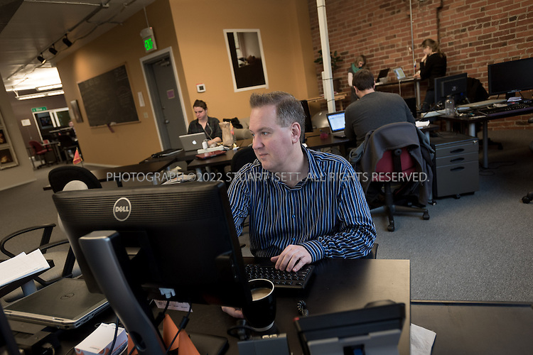 2/28/2014&mdash;Seattle, WA, USA<br /> <br /> Chris Hammersley, 42, a Seattle based e-commerce executive, working at his desk at Office Nomads, a coworking space in Seattle&rsquo;s Capitol Hill neighborhood.<br /> <br /> Hammersley is based in Seattle, but his company HQ is in Walnut Creek, Ca. and his bosses live in Chicago and Boston. When meetings take place, they can happen anywhere, so Chris uses coworking spaces in those cities and others when he travels for work. <br /> <br /> <br /> Photograph by Stuart Isett. <br /> &copy;2013 Stuart Isett. All rights reserved.