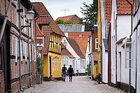 Couple strolling along traditional medieval street in Ribe centre, South Jutland, Denmark