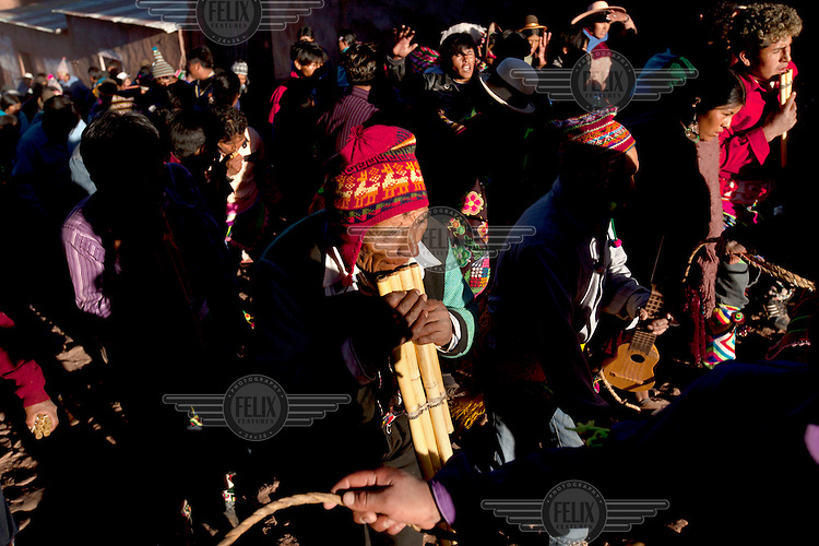 A man with a panflute plays traditional music as the people gather in the plaza of Macha during the tinku festival. <br /> <br /> The people of Macha and surrounding communities carry on the pre-Columbian tradition of ritual fighting. The communities gather on the plaza of Macha to fight and dance in competition with each other. The blood that is spilled is an offering to Mother Earth. In return, the people ask for rain and a good harvest. This ritual is called tinku or fiesta de la cruz since the cross is also engaged in the festivities. The cross is dressed up, given offerings and brought from communities around Macha to the church in town. This syncretic festival melds pagan, pre-christian rituals with Catholic practice. /Felix Features