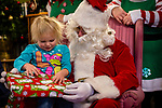 TORRINGTON, CT. 20 December 2019-122019BS09 - Dakota Secor, 3 of Torrington, left, starts to open up a gift given to her by Santa, as she sits on Santa's lap, during a visit by Santa at the FISH of Northwestern Connecticut Homeless Shelter in Torrington on Friday. Bill Shettle Republican-American