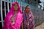 Bright pin, sarong clad women, Papagaran island, Komodo National Park