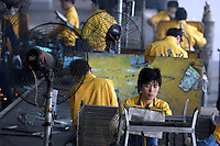 Woman on production line in a privately owned metal works factory, producing parts for major foreign companies including Fuji Xerox, Panasonic, Black & Decker and DeWalt, both for Chinese market and for export (including UK , US and Japan).