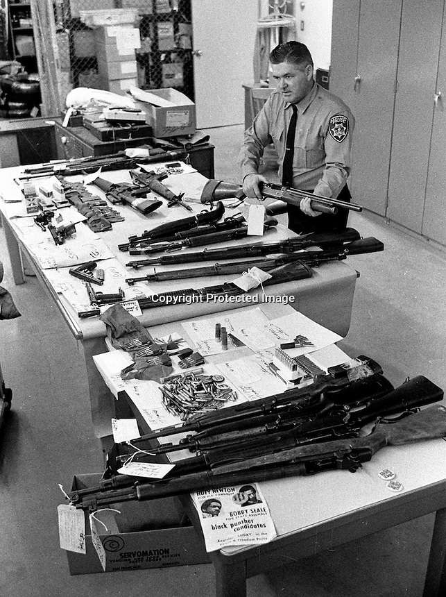 Oakland Police property clerk officer checks guns confiscated from the Black Panther's in Oakland, Ca..(photo 1968 by Ron Riesterer)