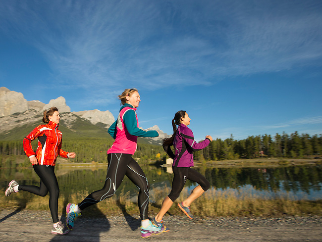Three women run along trails in the Canadian Rockies on a late summer morning in Canmore Alberta, Canada.  Photo by Gus Curtis.