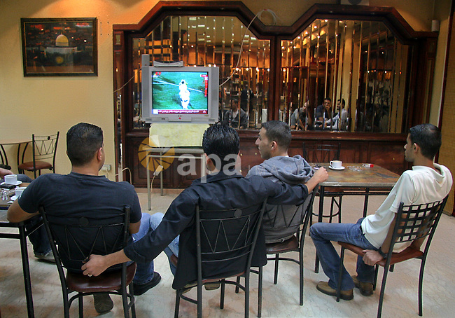 Palestinians watch their national football team play a friendly match against Jordan at a coffee shop in Gaza city. The new stadium trembled as thousands of Palestinians cheered their national football team in its first-ever home match near Jerusalem today. The Palestinians still long for their own state and an end to the decades-old Israeli occupation, but football fans were nevertheless able to share a rare moment of national joy in the cool autumn night.