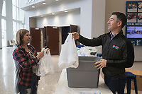 """Lead Pastor Mark Snodgrass (right) hands bags of toilet paper to Carlinda Pacheco of Bentonville (left), Monday, March 16, 2020 at the Bentonville Community Church in Bentonville. Pacheco, a member of SOCO Church, spent the day picking up bags to distribute to people at her own church. She said she was motivated to do this after seeing empty shelves at 19 different stores she visited in search of toilet paper. """"My husband says I'm the toilet paper dealer,"""" she said jokingly. Check out nwaonline.com/200317Daily/ for today's photo gallery.<br /> (NWA Democrat-Gazette/Charlie Kaijo)<br /> <br /> Lead Pastor Mark Snodgrass donated rolls of church surplus toilet paper after finding the shelves empty over the weekend following recent updates on the coronavirus.<br /> <br /> """"I remembered we had gotten a shipment of toilet paper. It's not gonna do us any good sitting in a closet, he said adding that the church had moved it Sunday services online.<br /> <br /> He said several people had stopped by to pick up some rolls and one person even picked up rolls to distribute to others at another church. In addition, he said as many people stopped by to donate rolls.<br /> <br /> """"People have donated about 100 rolls today. I've almost received as much as I've donated,"""" he said. """"We're a church and we believe this kingdom that christ invites us to is a kingdom of abundance. When we give we find he continues to give and bless us. We want to model that for our community. We're gonna get through this."""""""