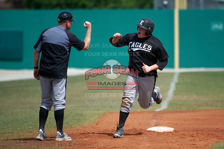Edgewood Eagles head coach Al Brisack fist bumps Garrett Bogucki (25) after a home run during the second game of a doubleheader against the Lasell Lasers on March 14, 2016 at Terry Park in Fort Myers, Florida.  Edgewood defeated Lasell 10-2.  (Mike Janes/Four Seam Images)