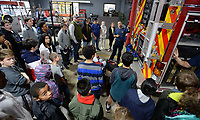 NWA Democrat-Gazette/ANDY SHUPE<br /> Levi Crandell with the Fayetteville Fire Department describes Wednesday, Nov. 6, 2019, the features of one of the department's engines for a group of student fire marshals from Fayetteville Public Schools at the department's central fire station. Schools in the district appoint student fire marshals who assist staff and students during fire drills and emergency situations by guiding people to exits and ensuring that doors are closed at their schools.