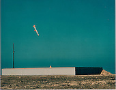 A Tomahawk cruise missile, configured with a live conventional warhead, demonstrated its terminal dive mode of attack in a test conducted on August 26, 1987.  The missile was launched from a submerged submarine underway off the coast of southern California and flew a land attack mission of more than 400 miles to its target, a concrete and steel structure the size of a warehouse with each concrete panel on the roof weighing 7,000 pounds.  The Tomahawk missile is approaching the target following a climb and rollover to attack at a dive angle which allows for increased effectiveness against a wider range of targets..Credit: DoD / CNP