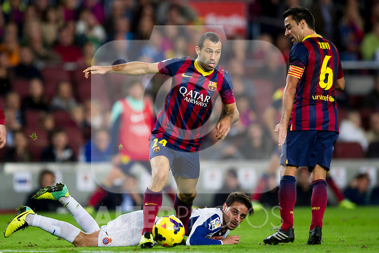 FC Barcelona's Javier Mascherano (left), Xavi Hernandez (right) and RCD Espanyol's Sergio Garcia (on the ground) during La Liga 2013-2014 match. November 1, 2013. (ALTERPHOTOS/Alex Caparros)