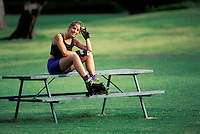 USA, Hawaii, Oahu, Kapiolani Park, young woman on picnic table in rollerblading gear.<br />
