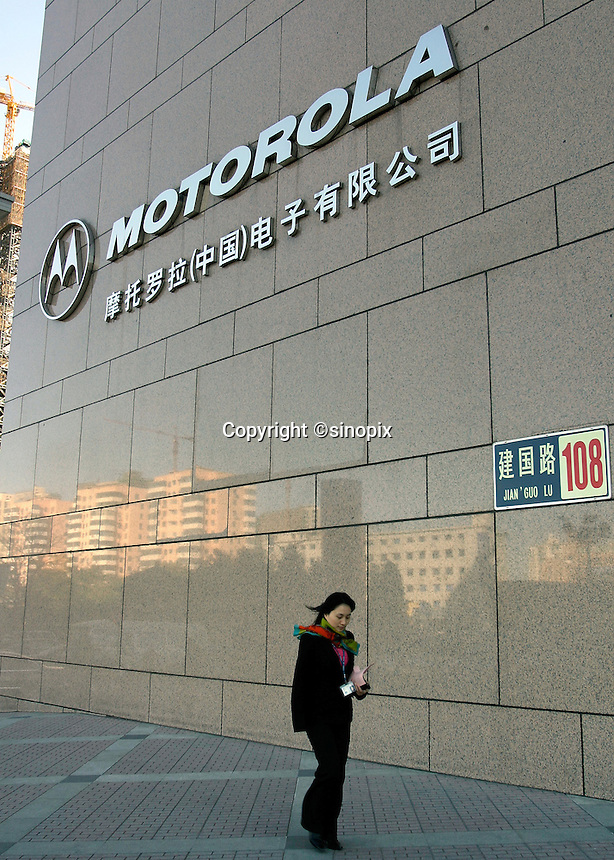 A woman walks past the Motorola Building in Beijing, China..16-NOV-04