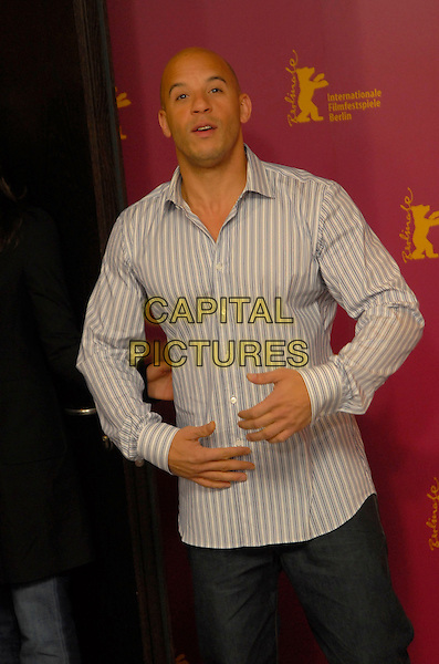 "VIN DIESEL .Photocall for ""Find Me Guilty"" at the 56th Berlin International Film Festival (Berlinale) in Berlin, Germany..February 16, 2006 .Ref: KRA.half length grey gray white striped shirt hands on stomach.www.capitalpictures.com.sales@capitalpictures.com.©Capital Pictures"