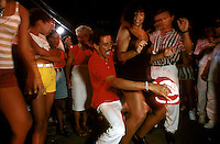 Samba school rehearsals reflect the party atmosphere that saturates every aspect of carnival. Two members of the Acadêmicos do Salgueiro group dance the sensuous samba as watchers form a ring around the couple.