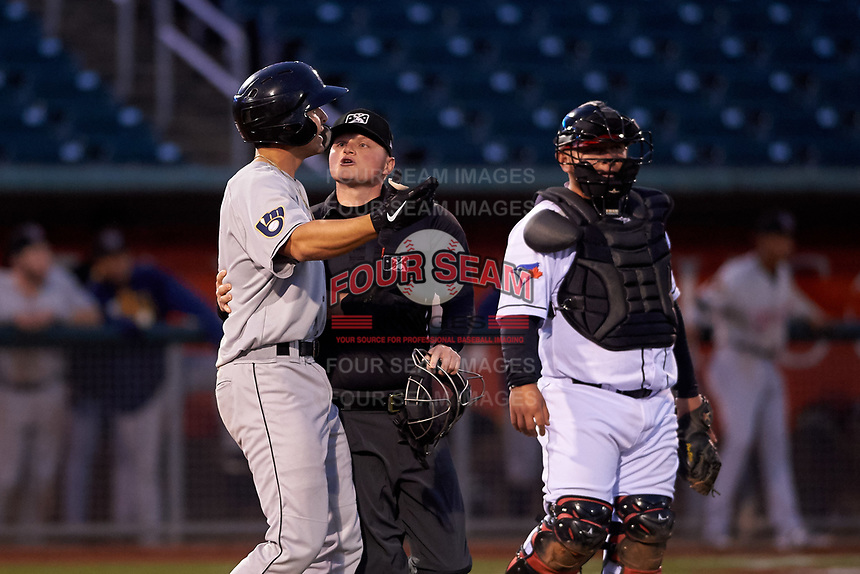 Wisconsin Timber Rattlers Brent Diaz (18) exchanges words with catcher Alejandro Kirk (23) while being held back by home plate umpire Lance Seilhamer during a Midwest League game against the Lansing Lugnuts at Cooley Law School Stadium on May 1, 2019 in Lansing, Michigan. Wisconsin defeated Lansing 2-1 in the second game of a doubleheader. (Zachary Lucy/Four Seam Images)