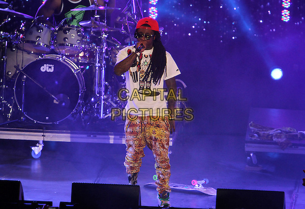 "Lil Wayne (Dwayne Michael Carter, Jr.).Caesars Entertainment Kick-Off Of ""Escape To Total Rewards"" , Los Angeles Show Held At Hollywood & Highland Center, Hollywood, California, USA, 1st March 2012..music concert gig live on stage  full 3/4 length singing  yellow print cap hat microphone singing white t-shirt  sunglasses trainers .CAP/ADM/KB.©Kevan Brooks/AdMedia/Capital Pictures."