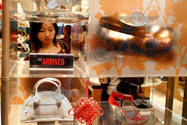 A woman browses handbags and shoes in a shop in Hong Kong.