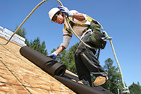 Pedro Vargas uses a harness and rope to make sure he is safe while rolling out tarpaper on the roof a new Quadrant Home in Mt. Vernon, Washington on August 4, 2006. The rope is attached to an anchor at the rooftop.