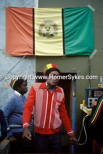 Young black Rastafarian dancing,  to a sound system under the Ethiopian Flag. Black community Notting Hill west London 1970s England UK