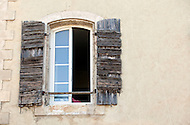 Old wooden shutters compliment a more modern window design on a home in Pernes-les-Fontaines, France