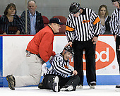 Larry Venis (BU - Trainer) and Dave Hansen check on Bob Bernard who was struck by a puck. - The visiting University of Vermont Catamounts tied the Boston University Terriers 3-3 in the opening game of their weekend series at Agganis Arena in Boston, Massachusetts, on Friday, February 25, 2011.