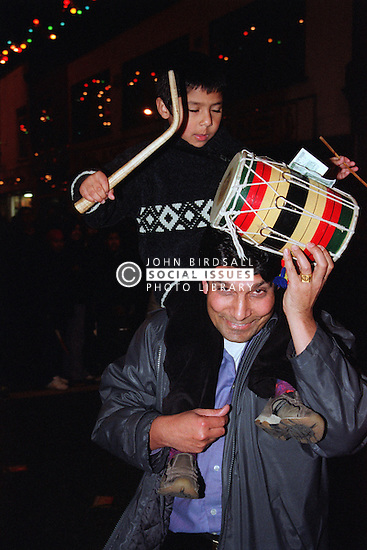 Father carrying young son on his shoulders who is playing traditional drum in celebration of Diwali; festival of light,