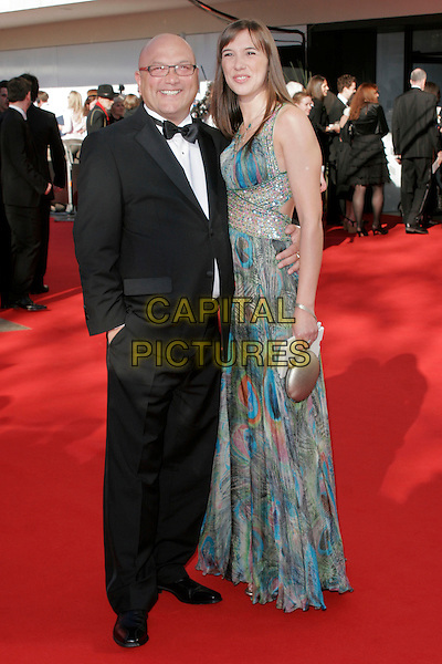 GREGG WALLACE & GUEST.Arrivals at the British Academy Television Awards 2009, Royal Festival Hall, London, England. .April 26th 2009 .TV Baftas bafta's full length greg black tuxedo hand in pocket long maxi dress blue pattern.CAP/AH.©Adam Houghton/Capital Pictures..