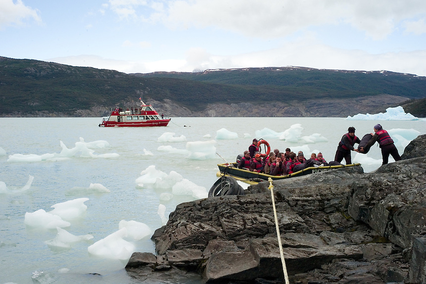 Hikers board a zodiac boat to be taken from the Refugio Lago Grey backcountry camp to a glacier tour boat waiting on Grey Lake, rear. Most hiked on the grand circuit at Torres del Paine National Park in southern Chile. Views of the glacier from below the John Garner pass are among the best in the park. (Kevin Moloney for the New York Times)