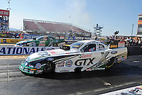 Feb. 17 2012; Chandler, AZ, USA; NHRA funny car driver Mike Neff (near lane) races alongside teammate John Force during qualifying for the Arizona Nationals at Firebird International Raceway. Mandatory Credit: Mark J. Rebilas-