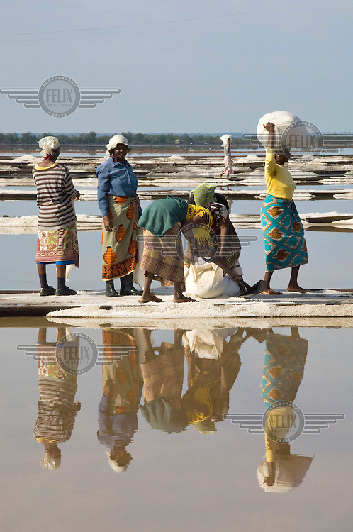 Women fill bags with sakt collected from a large salt pan in Matola.