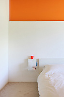 The simple bedroom has a signature wall of bright orange, a colour echoed in the glass on the suspended bedside table