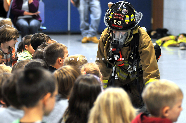 WINSTED, CT 14 OCTOBER 2011--101411JS01---Winsted firefighter Josh Harris, crawls around the floor so students at Batcheller Early Education Center in Winsted on Friday as they celebrate fire prevention week. The firefighters talked about the importance of fire safety before the students got to go outside to check out a fire truck. <br /> Jim Shannon Republican-American